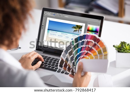 Close-up Of A Female Designer Holding Colorful Swatch Working On Laptop In Office #792868417