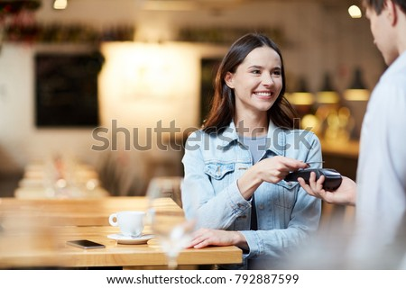 Young smiling woman with card holding it over payment terminal while paying for her order in cafe #792887599