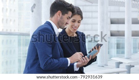 Business people use of smart phone together, showing others on smart phone outside office  #792931639