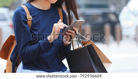 Woman look at mobile phone and holding shopping bag  #792936604
