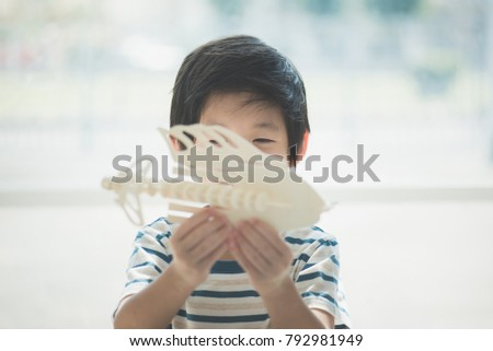 Cute Asian child  builds a toy of wood #792981949