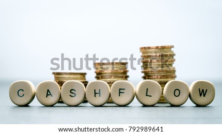 CASH FLOW letter block and stack coins, business concept. Royalty-Free Stock Photo #792989641