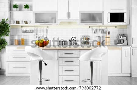 Modern kitchen interior with wooden table and microwave oven #793002772