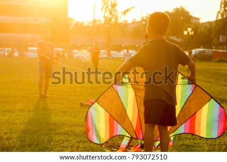 Teluk Intan, Malaysia; 7 January 2017: Chinese young boys preparing their kite to be flown at the field during sunset. #793072510