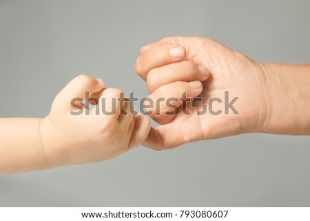 Hands of child and elderly man making pinkie promise on light grey background #793080607