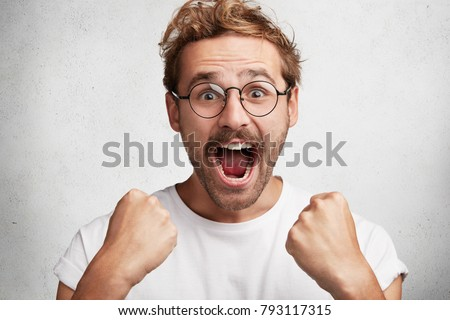 Excited happy man screams with happiness, celebrates his great triumph and victory, clenches fists, can`t believe in success, says: Wow, how great it is! Male champion achieves big effective results