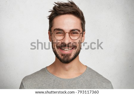 Headshot of satisfied cheerful handsome man grins at camera, glad to find suitable well paid job, isolated over white concrete background. People, positive emotions and facial expressions concept #793117360