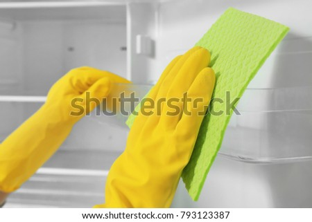 Woman cleaning refrigerator with rag, closeup #793123387