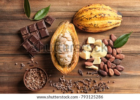 Composition with cocoa pod and products on wooden background, top view #793125286