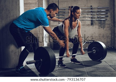 Young woman doing hard exercise at the gym with a coach. Royalty-Free Stock Photo #793136707