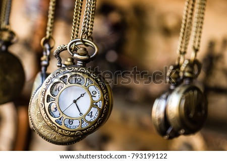 Vintage pocket watchs hanged with chains in an antique shop #793199122