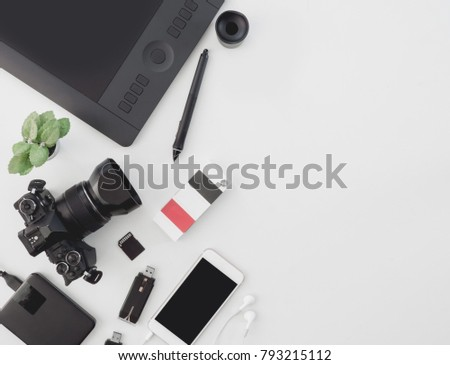 top view of photographer work station, work space concept with digital camera, book, memory card, smartphone, graphic tablet, external harddisk on white background #793215112