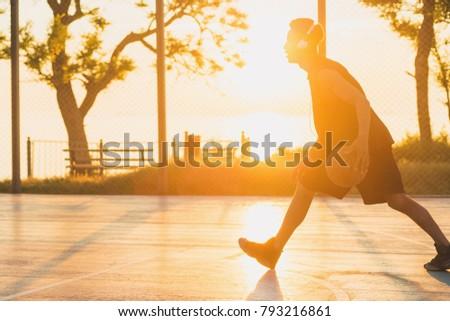 young black man playing basketball on court, morning exercises, active lifestyle, warm sunlight, doing sports on sunrise #793216861