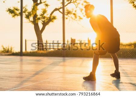 young black man playing basketball on court, morning exercises, active lifestyle, warm sunlight, doing sports on sunrise #793216864