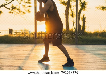 young black man playing basketball on court, morning exercises, active lifestyle, warm sunlight, doing sports on sunrise, silhouette #793216870