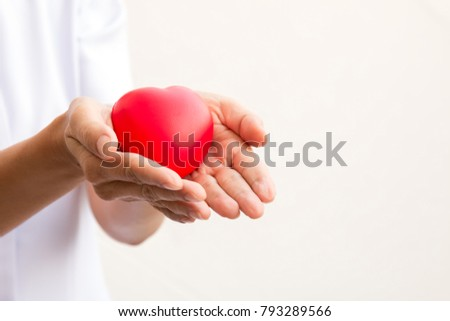 Nurse holding red heart in 2 hands; health care concept; love heart for valentine #793289566