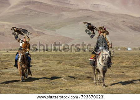SAGSAY, MONGOLIA - SEP 28, 2017: Eagle Hunter teaches her young daughter hunting with birds of prey to the hare in desert mountain of Western Mongolia. #793370023