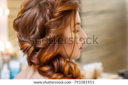 Beautiful, with long, red-haired hairy girl, hairdresser weaves a French braid, in a beauty salon. Professional hair care and creating hairstyles. #793381951