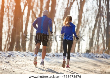 Young person's running in park together, back view  #793473676