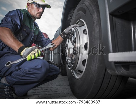 Semi Truck Wheel Maintenance. Caucasian Truck Mechanic with Large Wrench in Hand Taking Look at the Wheel in the Truck Service Center. #793480987
