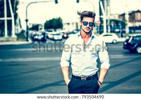 One handsome elegant young man in urban setting in European city, standing Royalty-Free Stock Photo #793504690