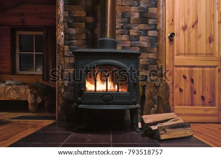Fragment of the interior of a country house. The iron furnace is heated. There is wood near the stove. It's dark outside the window. #793518757