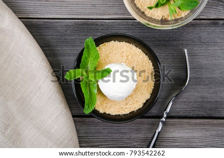 Top view close up Apple crumble dessert with vanilla ice cream, green mint on grey wooden table. fork with cake on tablecloth #793542262