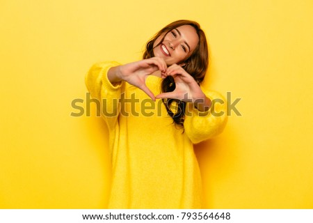 Smiling young girl in yellow sweater showing heart with two hands, love sign. Isolated over yellow background. Royalty-Free Stock Photo #793564648