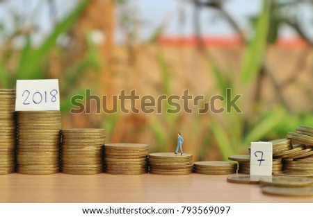 """Miniature businessman walks on roll ladder of gold coins to """"2018"""" word on paper from unstable roll coin on wood table in blur natural tree                #793569097"""