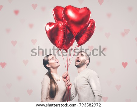 Valentine Couple. Portrait of Smiling Beauty Girl and her Handsome Boyfriend holding bunch of heart shaped air balloons and laughing. Happy Joyful Family. Love. Happy Valentine's Day #793582972