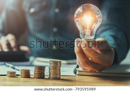 business man hand holding lightbulb with using calculator to calculate and money stack. idea saving energy and accounting finance in office concept #793595989