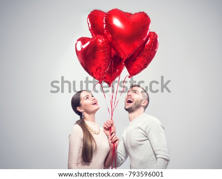 Valentine Couple. Portrait of Smiling Beauty Girl and her Handsome Boyfriend holding bunch of heart shaped air balloons and laughing. Happy Joyful Family. Love. Happy Valentine's Day #793596001
