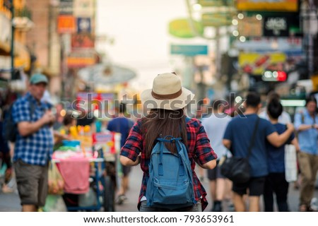 Back side of Young Asian traveling women walking and looking in Khaosan Road walking street in evening at Bangkok, Thailand, traveler and tourist concept Royalty-Free Stock Photo #793653961