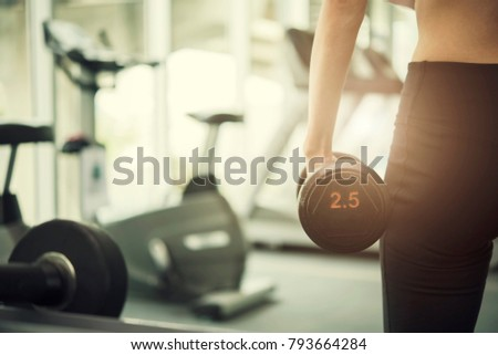 Sport woman holding dumbbell on her hand at gym or sport club with sunlight in morning. Healthy background concept. Picture for add text message. Backdrop for design art work. #793664284