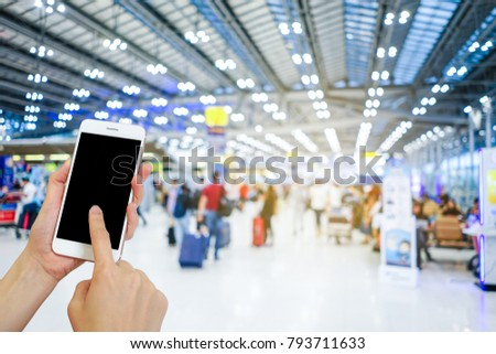 Hand holding mobile phone with airport terminal blurred crowd of Travelling people on the background, Bokeh light, Social network, internet,Traveling concept #793711633