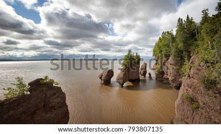Panorama of the flowerpot rock formations at Hopewell Rocks, Bay of Fundy, New Brunswick. The extreme tidal range of the bay makes the sea look like mud from the stirred up silt.  #793807135