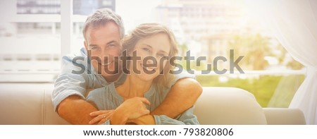 Content man hugging his wife on the couch smiling at camera at home in the living room #793820806