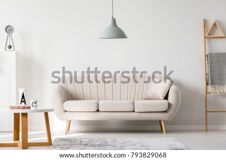 Gray lamp above beige couch in sophisticated living room interior with ladder and wooden round table #793829068