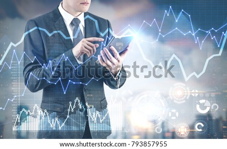 Unrecognizable young businessman wearing a dark suit with a tie and working with a digital tablet. HUD and graphs. Toned image double exposure mock up #793857955