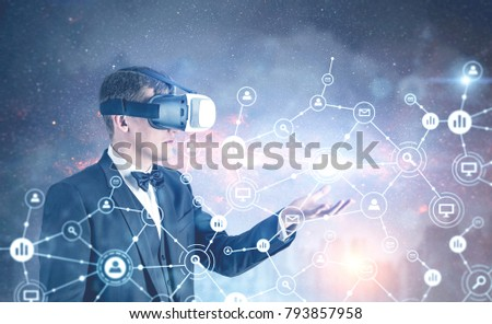 Side view of a fair hair businessman wearing VR glasses, a bow tie and a suit showing a network hologram in a city sky. Toned image double exposure mock up Elements of this image furnished by NASA #793857958