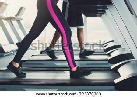 Side view of attractive young unrecognizable woman in leggings running on treadmill in gym. Female slim legs jogging in fitness club. Healthy lifestyle concept #793870900