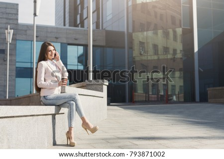 Smiling businesswoman talking on smartphone outdoors. Caucasian executive taking a city walk at lunch time, drinking take away coffee, sitting outdoors near modern office center #793871002