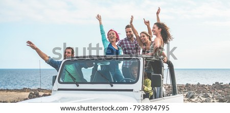 Happy tourists friends doing excursion in desert on convertible jeep car - Young people having fun traveling together - Friendship, youth lifestyle and vacation concept - Focus on guys with hands up #793894795