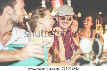 Group of happy friends drinking cocktails and laughing at beach party outdoor - Young tourist having fun in summer vacation - Focus on left girl eye - Nightlife, holidays and youth concept Royalty-Free Stock Photo #793901242