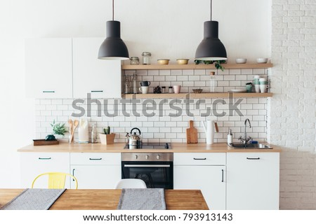 Modern new light interior of kitchen with white furniture and dining table. Royalty-Free Stock Photo #793913143