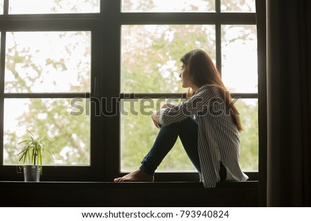 Thoughtful girl sitting on sill embracing knees looking at window, sad depressed teenager spending time alone at home, young upset pensive woman feeling lonely or frustrated thinking about problems Royalty-Free Stock Photo #793940824