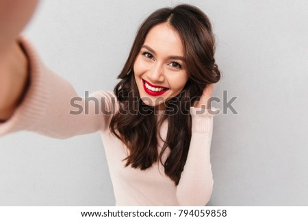 Studio portrait of beautiful woman smiling with white teeth and making selfie, photographing herself over gray background