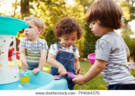 Group Of Young Children Playing With Water Table In Garden #794064370