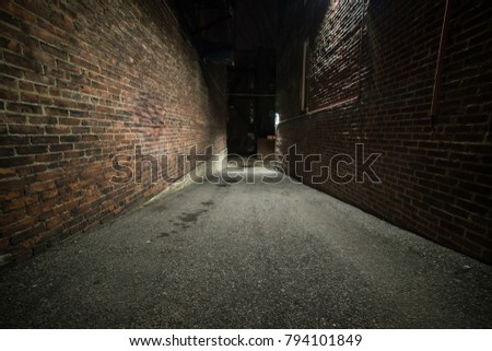 Scary empty dark alley with brick walls Royalty-Free Stock Photo #794101849