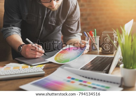 Young creative artist of web design in hat with graphic tablet in modern loft office #794134516